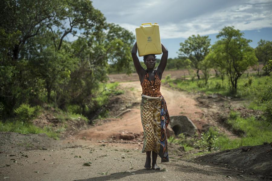 Beatrice portant de l'eau, dans le camp de réfugiés d'Imvepi. Photo : Kieran Doherty/Oxfam