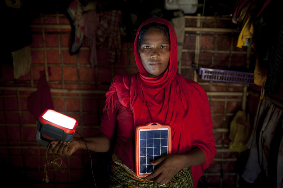 Rohingya refugee Asia Bibi* with solar panels provided by Oxfam, in her shelter in the camps in Cox's Bazar, Bangladesh. Photo: Abbie Trayler-Smith/ Oxfam