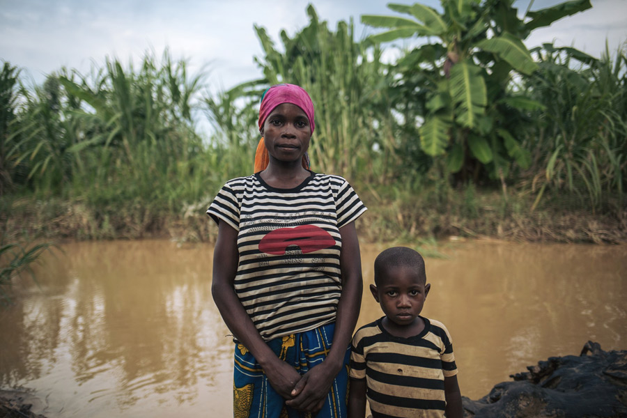Rizini fetches water to the contaminated river in Malinde village three times a day with her four-year old son, Jack.