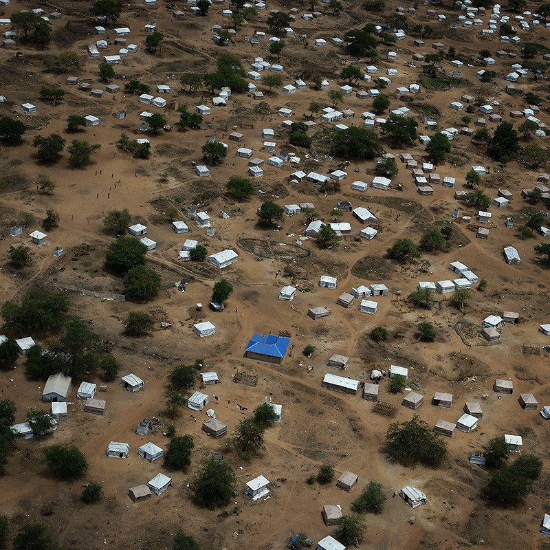 An aerial view showing tents and small buildings scattered across a savanna landscape