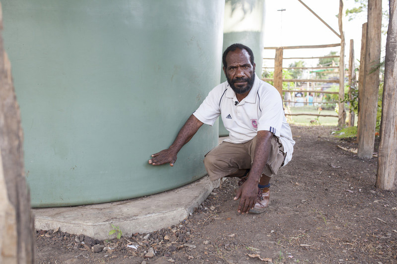Community leader Silas Orrocco shows the water level in one of his village's two 90,000 litre water tanks. Photo: Rodney Dekker/Oxfam