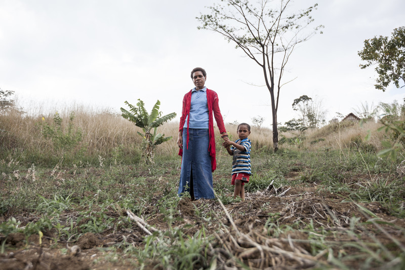 Paku Dick, 25, with her son Dixon, 4, in her sweet potato plot impacted by drought and pests. Photo: Rodney Dekker/Oxfam