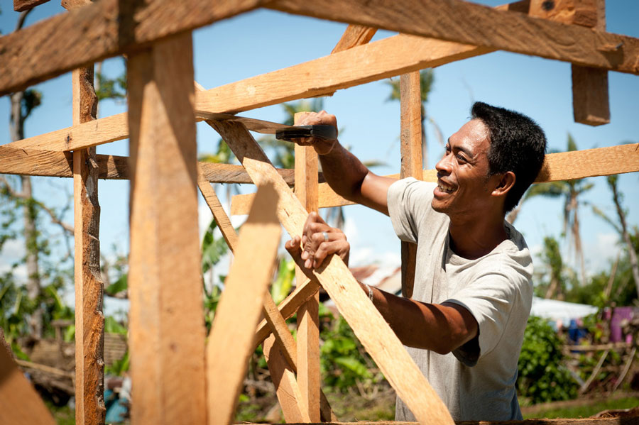 Larry Tondo (31) Carpenter and Chainsaw Operator, builds a coconut lumber sales kiosk, 3 months after Haiyan Typhoon hit the Philippines. Photo: Eleanor Farmer/Oxfam