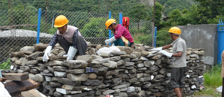 Lhakpa Dolma Lama (first from left) stacks stones at the premises of Golma Devi School in Timbu of Sindhupalchowk. Photo: Oxfam