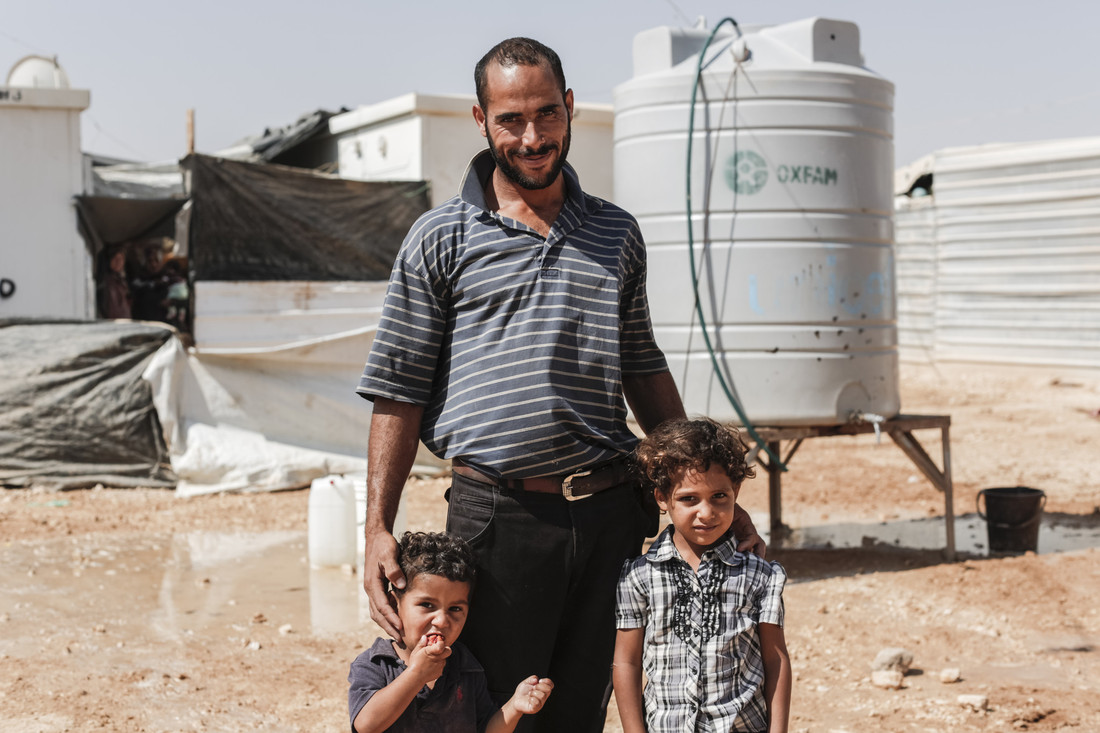 Mohammad Naser, a father of 3 from Ghouta, near Damascus in Syria, collecting drinking water from an Oxfam supplied water tank in Zataari camp in Jordan. Mohamad used to sell vegetables in a supermarket in Syria. Photo credit: Sam Tarling / Oxfam