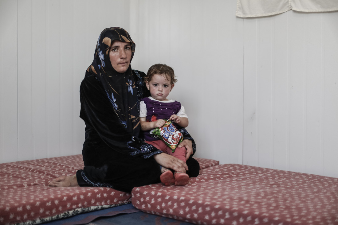 Sanaa, an Oxfam volunteer from Deraa in Syria holds her daughter Amna inside their caravan in Zataari camp in Jordan. Photo credit: Sam Tarling/Oxfam