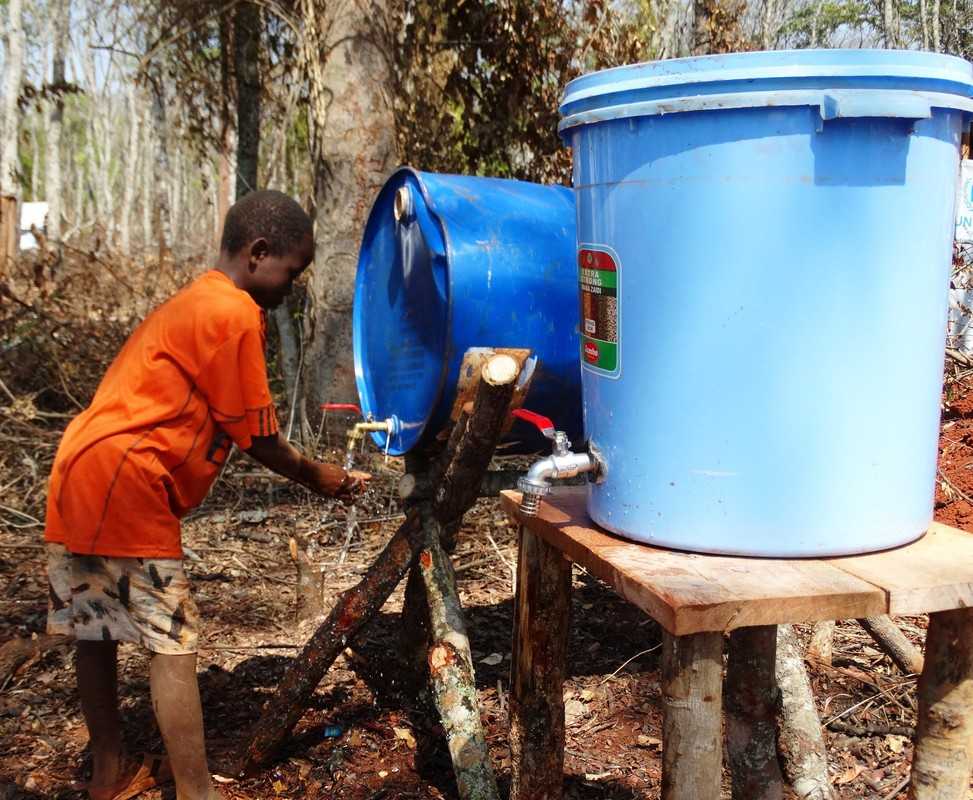 A boy washes his hands at an Oxfam hygiene station, Nduta camp, Tanzania.