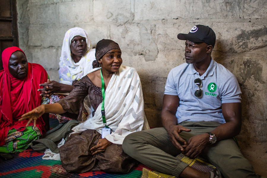 Djimon Hounsou listens to a woman who has lost her husband during the conflict with Boko Haram and the military.
