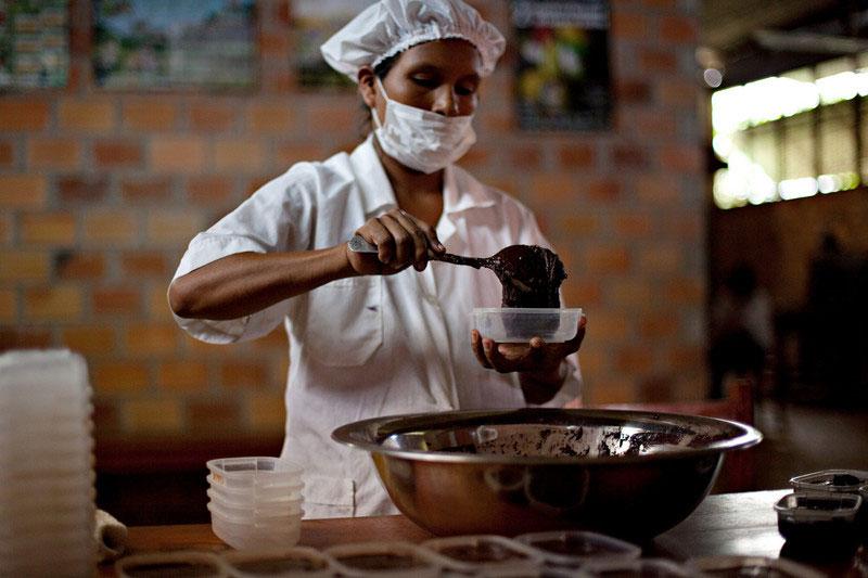 Una trabajadora de la planta transformadora de cacao APARAB, Bolivia, rellenado un bote de pasta de cacao. Foto: Oxfam / Patricio Crooker