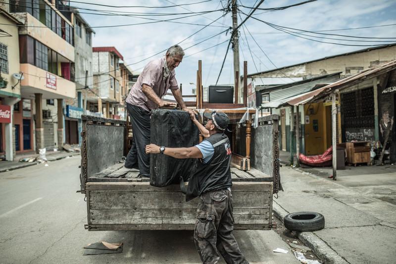 Luis Toral carga en un camión algunas de las pertenencias que ha podido recuperar tras el terremoto, Portoviejo.