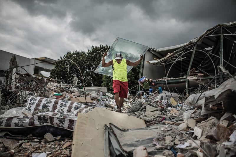 Jonatan recupera un cristal en buen estado de un edificio destruido que usará para arreglar su casa en Portoviejo.