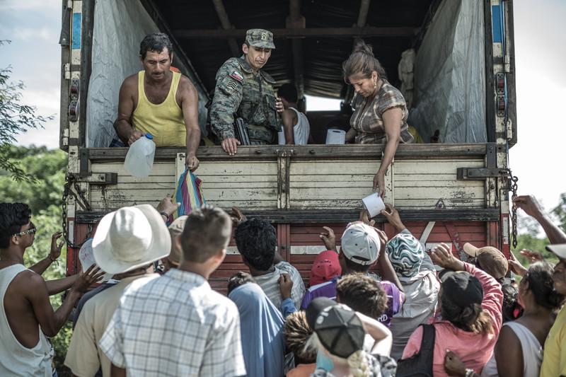 Un grupo de personas recibiendo artículos de primera necesidad en el albergue temporal de la comunidad de Canoa.