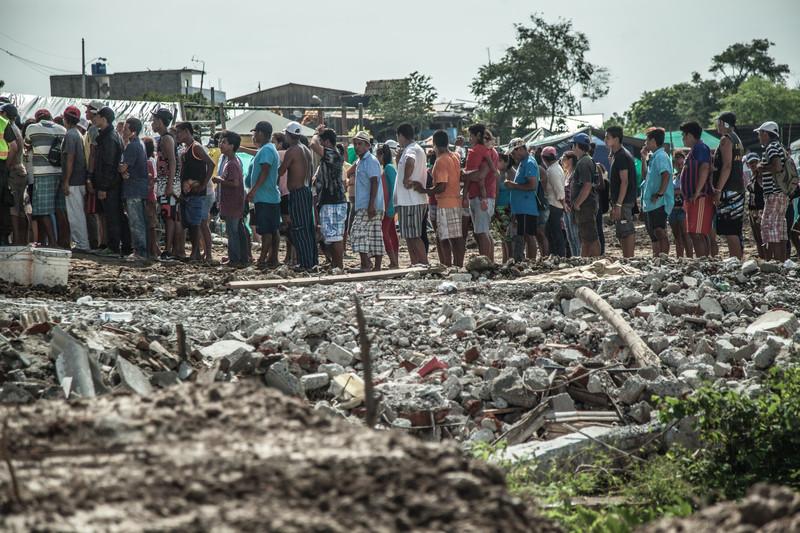 Un grupo de gente espera a que se distribuya agua potable y alimentos en Canoa.