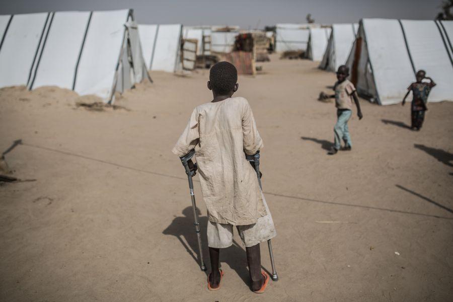Un niño con una pierna ortopédica frente a su refugio, campo de Muna Garage. Photo: Pablo Tosco/Oxfam