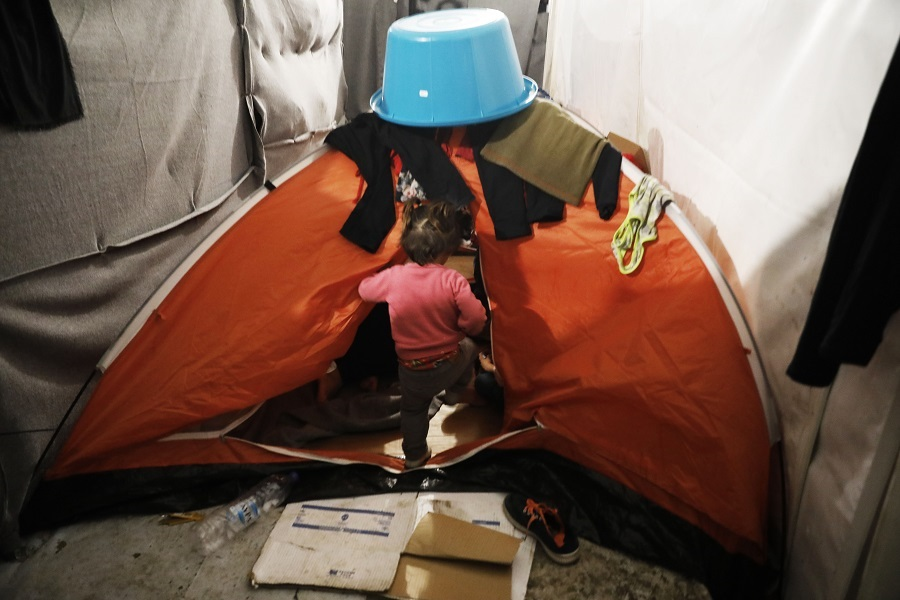 Dozens of people, including very young children, are crammed into summer tents with only a canvas cloth separating one family from another.