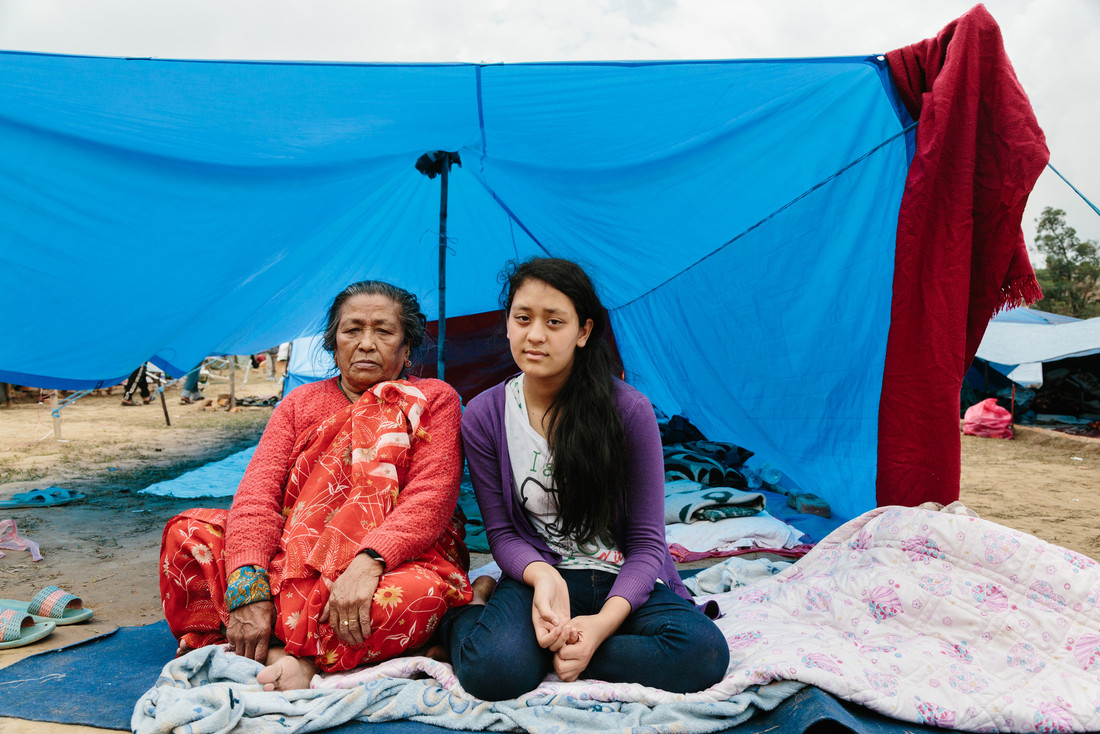 An elderly woman and a girl sit on blankets in front of a tarpaulin.