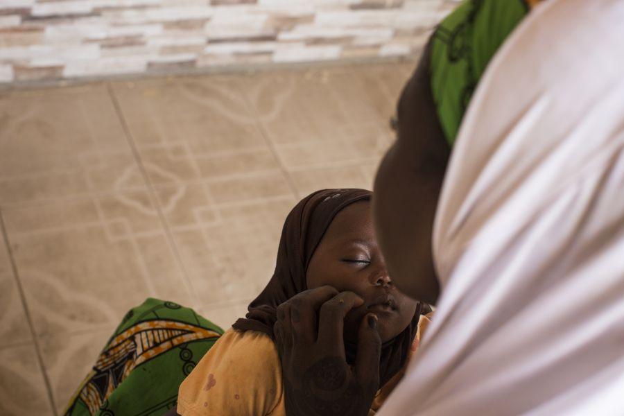 Kadija*, 18, holds her baby at a house in Maiduguri, Nigeria.