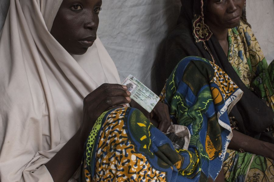 Bintu*, 30, a mother of five from Soya, near the town of Bama, holds her husband's ID card.