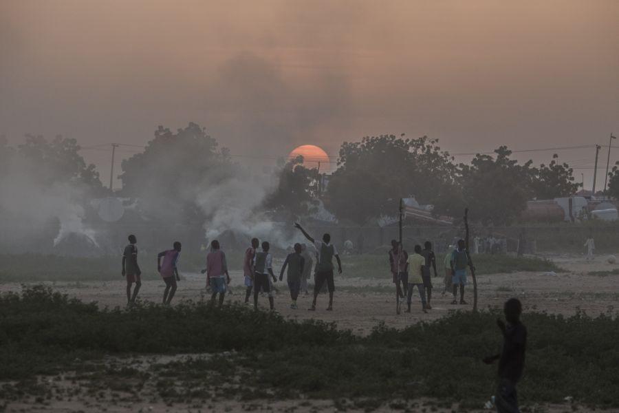 Des enfants jouent au football alors que le soleil se couche derrière la fumée des feux de charbon dans le camp pour déplacés de Kushari, près de Maiduguri, la capitale de l'Etat de Borno. Photo: Sam Tarling/Oxfam