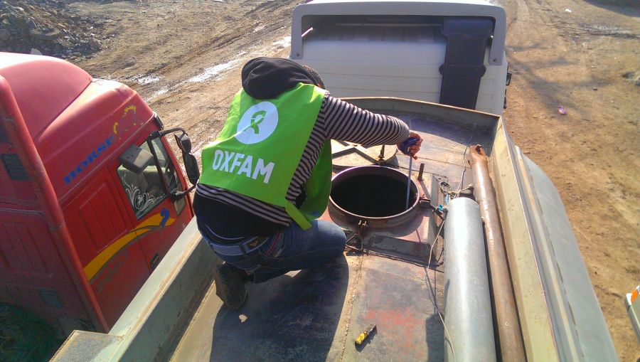 An Oxfam volunteer monitors the trucked water before it is pumped to the main water reservoir in Herjalleh, Rural Damascus.
