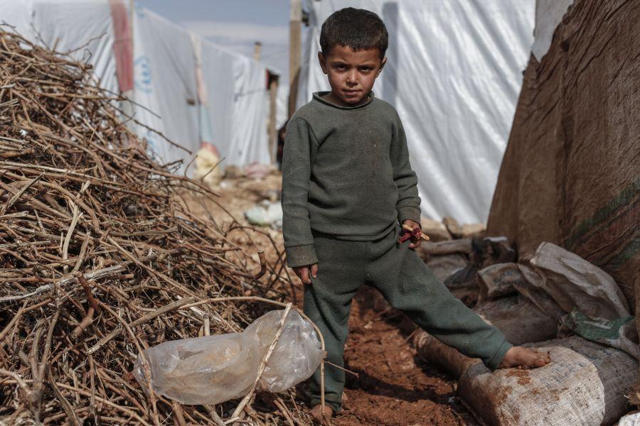 Malik, 7 ans, se tient nu-pieds dans la boue, dans un campement sauvage de réfugiés syriens, dans la plaine de la Bekaa, au Liban..