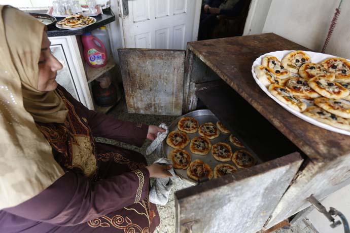 A woman prepares pastries, in Gaza