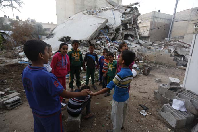 Children form a circle, in the middle of rubble, in Gaza
