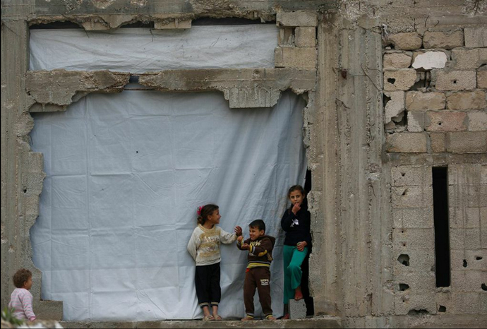 Young children at their badly damaged home, its missing wall covered with tarpaulin, in Gaza