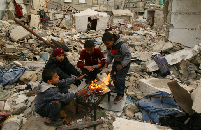 Children gathered around a fire, in the middle of rubble, in Gaza