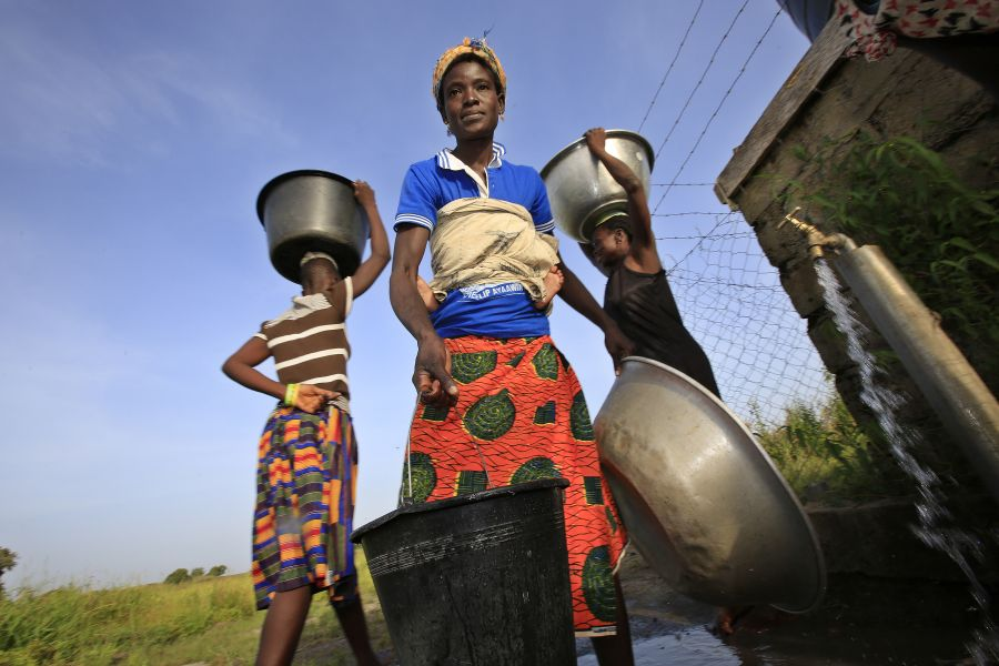 Felicia Ayaawin draws water from the well Oxfam's partner installed near her home in Kpatua. The well has an electric pump powered by solar panels, and water is stored in a large tank.