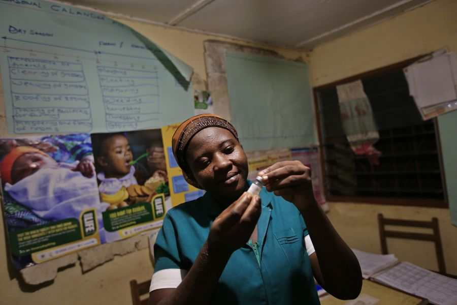 Latana Ganda, the nurse in Kpatua's clinic, inspects a vaccine she stores in a solar-powered refrigerator.