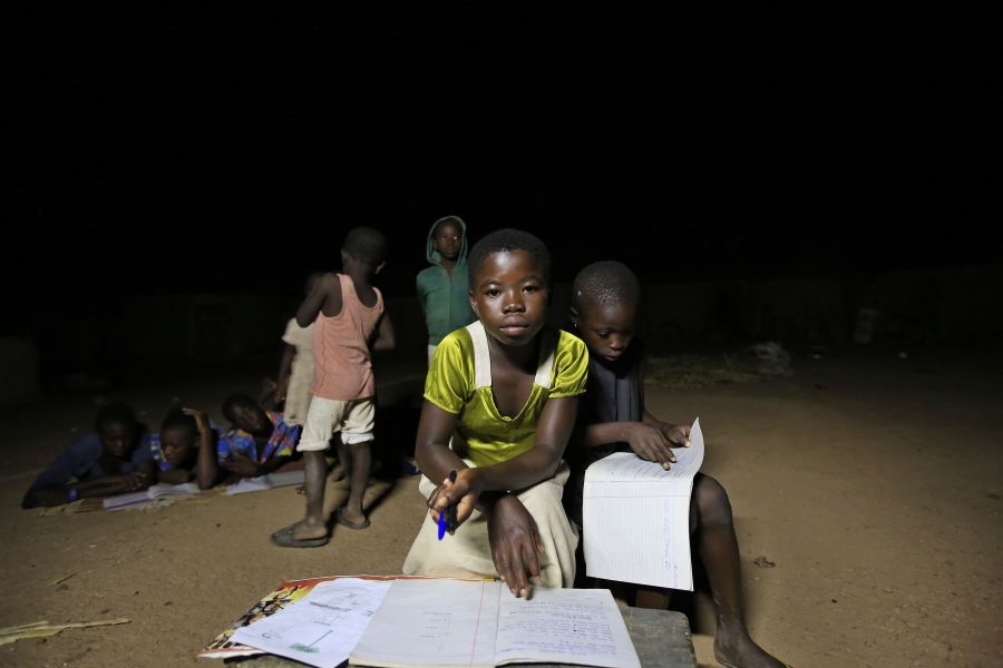 Children study by the light of a solar-powered lamp at the home of Mbil Ayaaba, chief of Kpatua village.