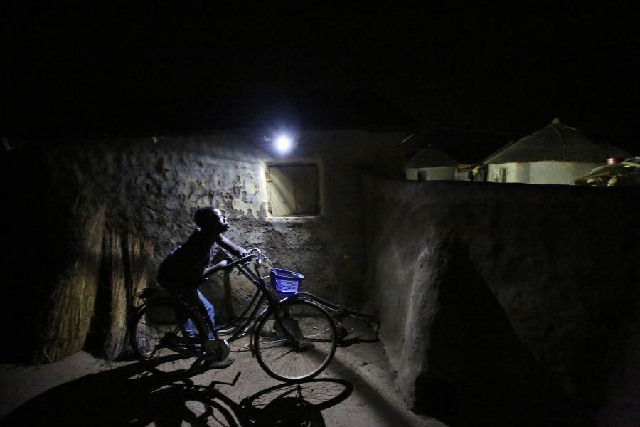 A boy passes by a motion-activated LED light in Kpatua village. The solar energy system at this home generates and stores electricity for night-time use.
