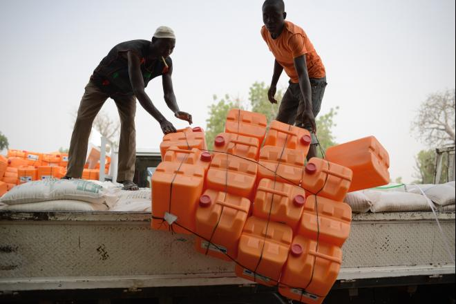 Jerry cans for carrying and storing water are offloaded from a truck in Yola.