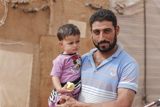 Jemaa Al Halayal, de 35 años, sostiene a su hija de dos años, Amina*, delante de la tienda en la que viven en un asentamiento informal en el norte del Valle de la Bekaa, en el Líbano. Huyó de Siria hace dos años junto a su mujer.