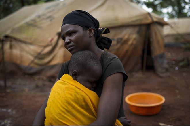 Aline, una refugiada burundesa, sentada junto a su hija más pequeña, Gloriose*, fuera de su tienda en el campo de refugiados de Nyarugusu (Tanzania). En abril de 2015, debido al conflicto, se produjo un aumento en la llegada de refugiados de Burundi.