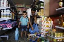 In a store aisle, a young boy looks into the camera while his father packs food into plastic bags.