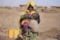 Fathima gives her son a drink of clean water, provided by Oxfam , Ethiopia