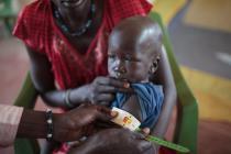 George (prénom modifié) sur les genoux de sa mère pendant que le personnel sanitaire évalue son état nutritionnel, au Soudan du Sud.