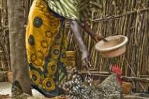 A woman feeding chickens in Tanzania. Photo: Oxfam