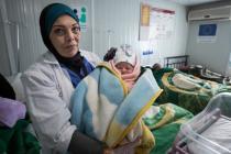 A doctor hold a new born baby, Za'atari Refugee Camp, Jordan