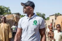 Djimon Hounsou walks through a street in Jakana leading to one of the camps that people who have fled their homes now live.