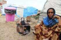 Une femme prépare du thé dans un camp pour déplacés au Yémen. Avec le pain, c'est à présent tout ce qui constitue le régime alimentaire pour des millions de Yéménites. Photo: Hind Aleryani/Oxfam