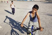 A boy cycles through the West Bank
