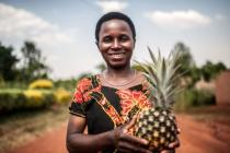 Mukeshimana Leocadie holds a pineapple outside Tuzamurane cooperative centre in Eastern Rwanda, Kirehe District where she is a member.