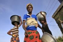 Felicia Ayaawin puise de l'eau dans le puits installé par le partenaire d'Oxfam près de sa maison à Kpatua.