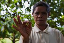 Sal Hnok holds a shell casing from a bullet fired at him when he insisted workers stop clear cutting the forest near his village in northern Cambodia.