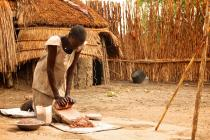 Nyamor Nwat grinds the millet to feed her family, in Lankien, South Sudan. Photo: Oxfam