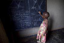 A girl is writing on a black board, in a school in Rwanda. Photo: Simon Rawles/Oxfam