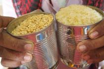 Shopkeeper Ala'a Abdhullah Farag Wans, fills cans of rice and grain -each contains 500 grams.  Photo: Caroline Gluck/Oxfam